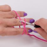 Push the crochet hook under the thread at the bottom and hook the thread at the top with the crochet hook.